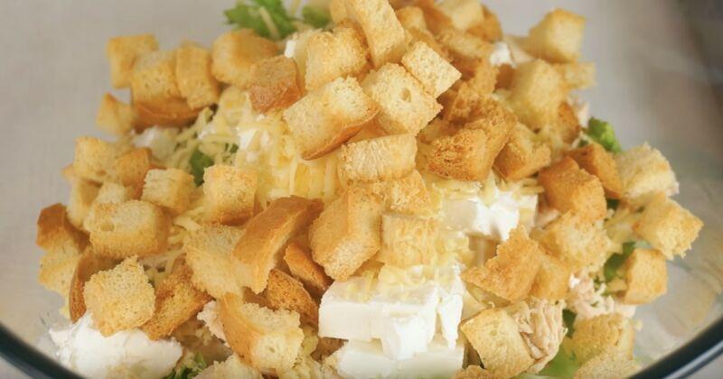 добавляем в салат брынзу, сыр и сухарики