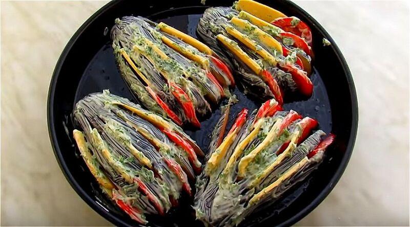 укладываем баклажаны на противень и вкладываем в них помидоры с сыром