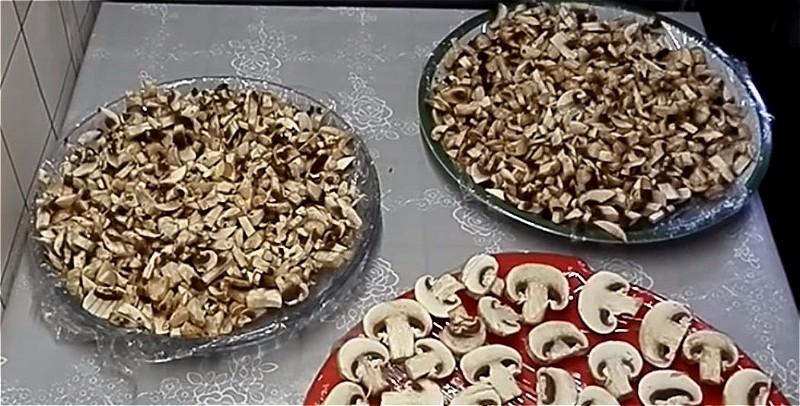 нарезаем шампиньоны и раскладываем на блюдо с пищевой пленкой
