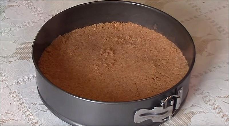 Печенье измельчаем, соединяем с масло и выкладываем в форму