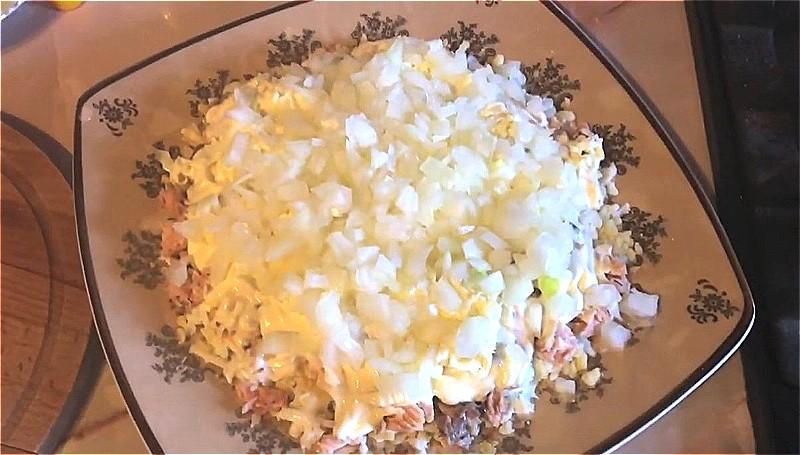 натираем сливочное масло и выкладываем на майонез, затем слой лука